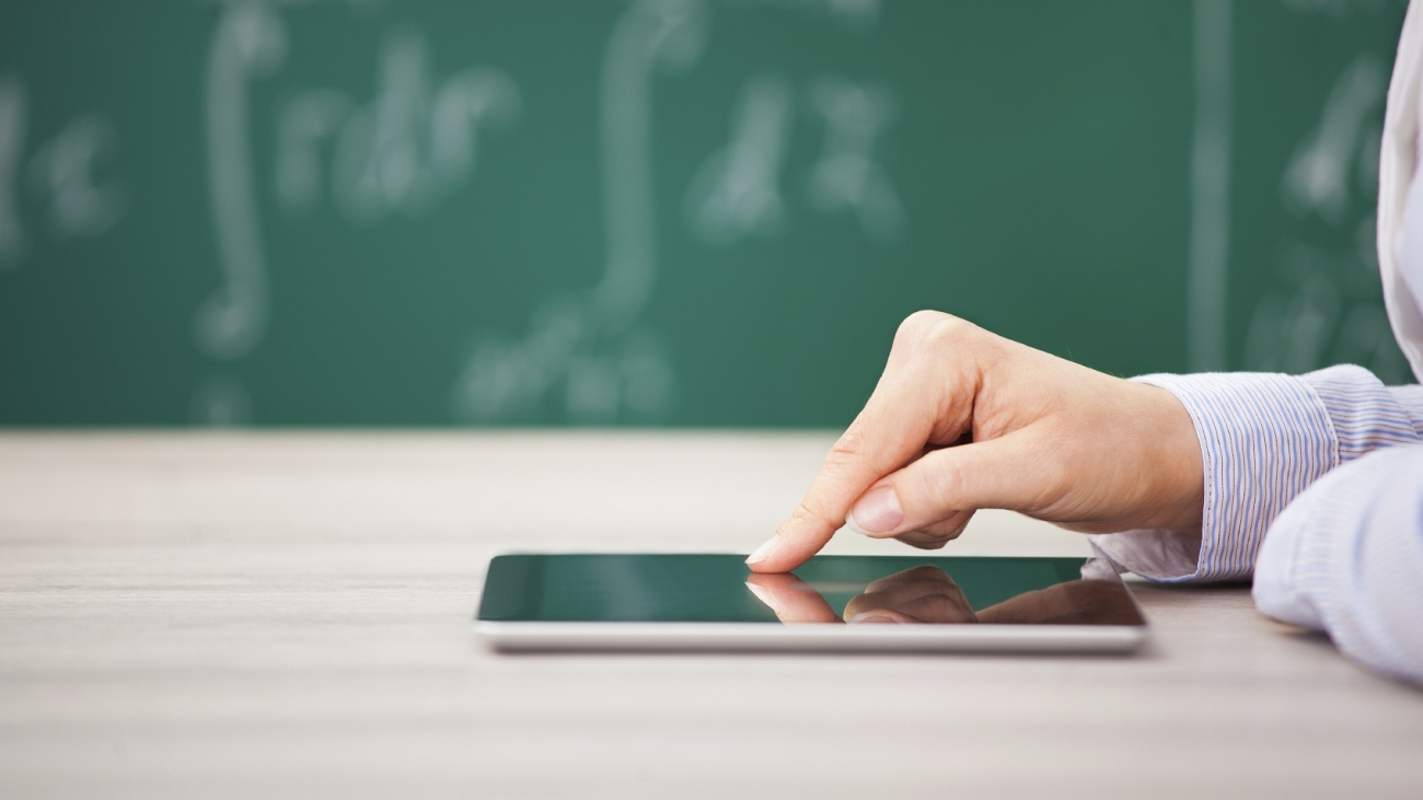 Close-up Of Hand Over Digital Tablet Screen In Front Of Chalkboard